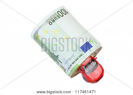 A red metal car inside a roll of banknote money isolated on white