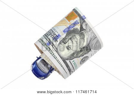 A navy blue metal car inside a roll of American Dollar banknote money isolated on white