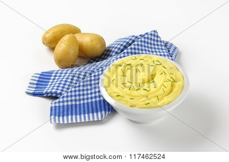 bowl of mashed potato puree with chopped chives and raw potatoes