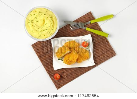 bowl of mashed potato puree with chopped chives and plate of breaded turkey breast on brown place mat