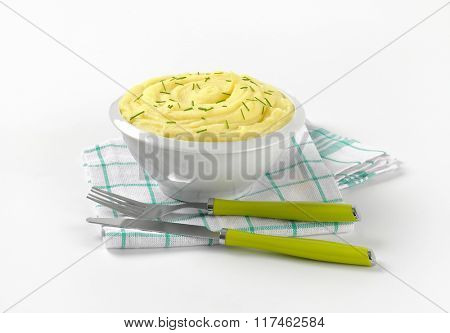 bowl of mashed potato puree with chopped chives and cutlery on checkered dishtowel