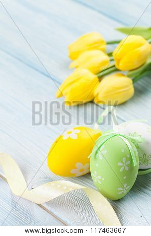 Easter eggs and yellow tulips over wooden background with copy space