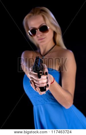 A woman wearing blue dress in sunglasses with gun on black background