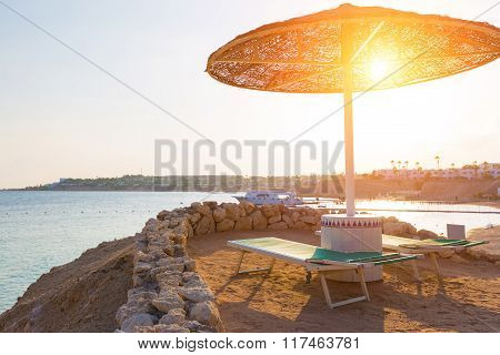 Umbrellas and empty deckchairs on the beach during sunset