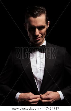 portrait of smiling elegant man posing in dark studio background while closing his black jacket and looking at the camera