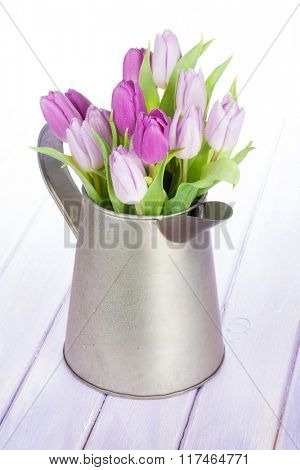 Purple tulip bouquet in watering can on wooden table