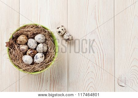 Easter eggs in nest over wooden background. View with copy space