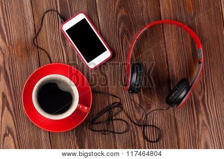 Smartphone, headphones and coffee cup over rustic wooden table. Top view