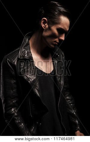 side portrait of confident rocker in leather jacket posing in dark studio background looking down