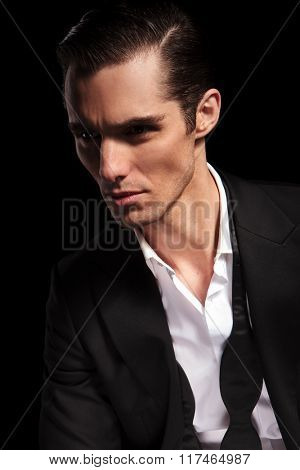 portrait of handsome businessman with open shirt looking away in dark studio background