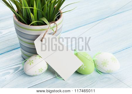 Easter eggs and potted plant on wooden background with tag for copy space