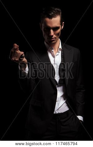 portrait of classy man in black tuxedo with hand in pocket snapping fingers while posing in dark studio background