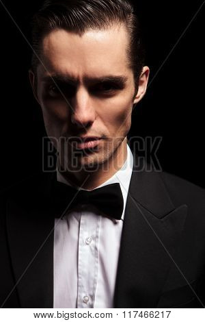 close portrait of classy man in tuxedo with bowtie posing in dark studio background looking at the camera