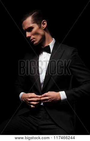 portrait of confident businessman in black suit with bowtie posing seated in dark studio background while closing his jacket and looking away