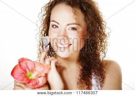 Beautiful spa girl holding pink flower and brush