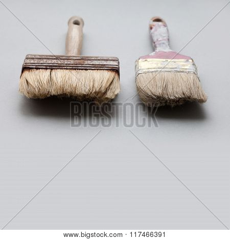 Pair of used, aged paintbrushes on gray background. Painter brush texture, macro view,  copy space