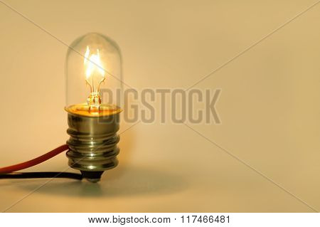 Glowing light bulb. Retro style filament lightbulb with electric wires on yellow background. Macro v