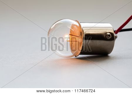 Lightbulb with electric wire laying on gray background. Ideal spherical surface. Glowing filament bu