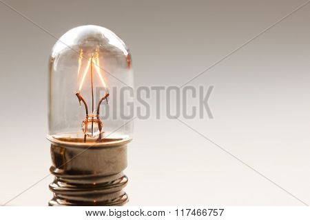 Close up glowing light bulb, Retro style filament lamp macro view. Warm colors background. Soft focu