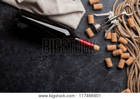 Red wine bottle, corks and corkscrew over dark stone background. Top view with copy space