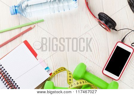 Health and fitness concept. Dumbbells, water bottle, smartphone, headphones and notepad. Top view with copy space