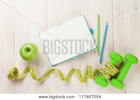 Diet and fitness concept. Dumbbells, apple, tape measure and notepad for copy space