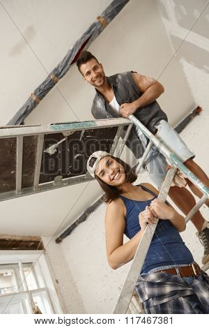 Young couple standing on scaffold, renovating home, smiling happy.