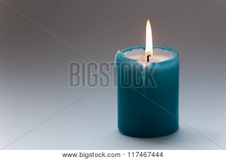Turquoise candle on gray gradient background. Macro view. soft focus. Memorial day concept. copy spa