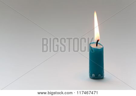 Burning candle with natural flame. Turquoise color. Simplicity concept Life symbol. Close-up, Shallo