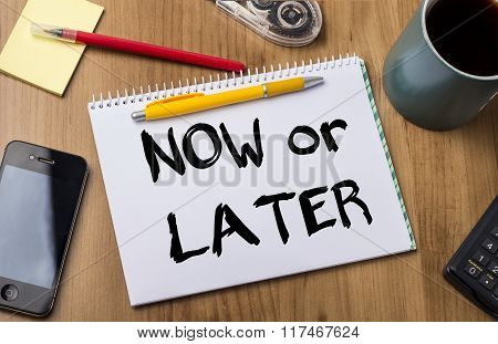 Now Or Later - Note Pad With Text On Wooden Table