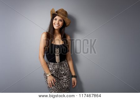 Pretty young woman smiling in straw hat, looking at camera.