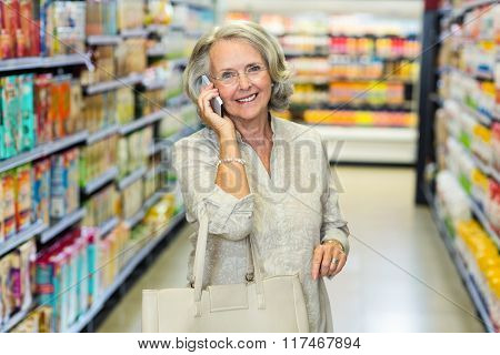 Smiling senior woman on phone call at the supermarket