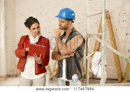 Client and contractor talking at renovation site, using tablet computer.