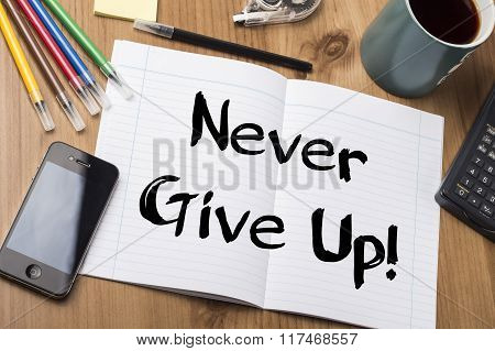 Never Give Up! - Note Pad With Text On Wooden Table