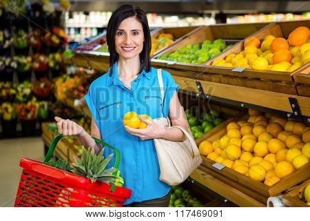 Portrait of a smiling woman with a basket in supermarket