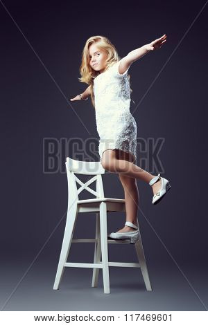 Fashion shot of a pretty little girl with beautiful blonde hair wearing white dress. Studio shot. Kid's beauty, fashion.