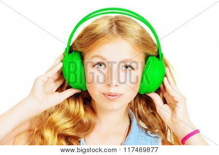 Modern teenager girl listening to music in headphones. Studio shot. Isolated over white. Copy space.