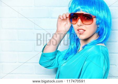 Fashion girl in bright blue wig and sunglasses posing by the urban white brick wall. Beauty, fashion.