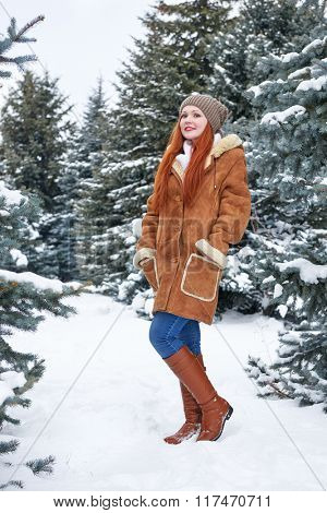 Girl in winter park at day. Snowy fir trees. Redhead woman full length.