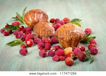 Muffins, Scattered Around The Raspberries, Strawberries, Mint Leaves On Turquoise Background