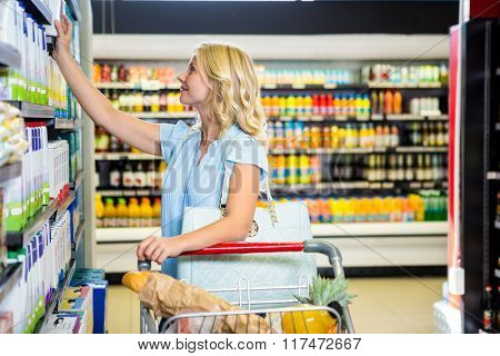 Smiling woman picking dairy products at supermarket