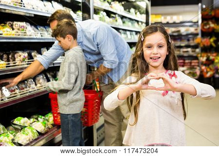 Smiling daughter making heart shape in grocery store