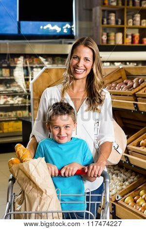Smiling mother and son with cart in grocery store