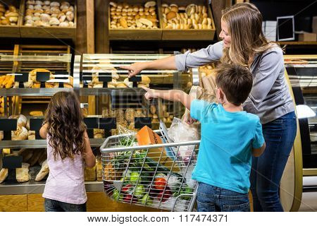 Happy family looking at bread in grocery store