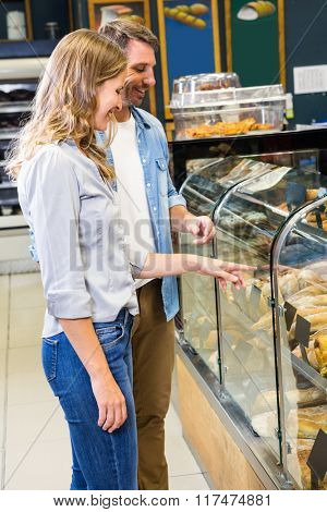 Happy couple looking at bread in grocery store
