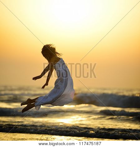 young woman jumping on the beach in summer evening
