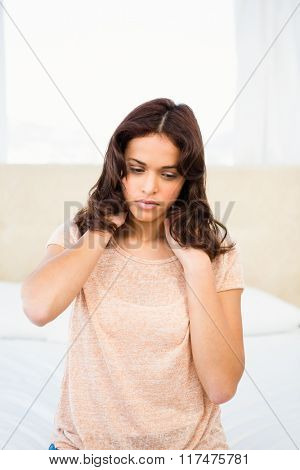 Casual woman with neck pain sitting on her bed at home