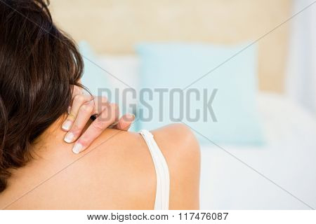 Rear view of a woman with neck pain at home