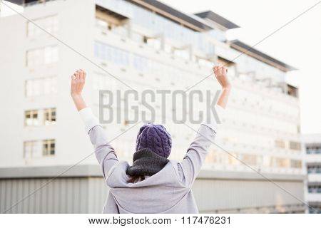 Happy woman raising her hands up outside