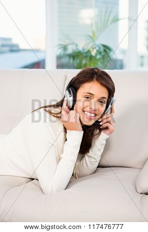 Pretty woman listening with headphones to music lying on couch at home